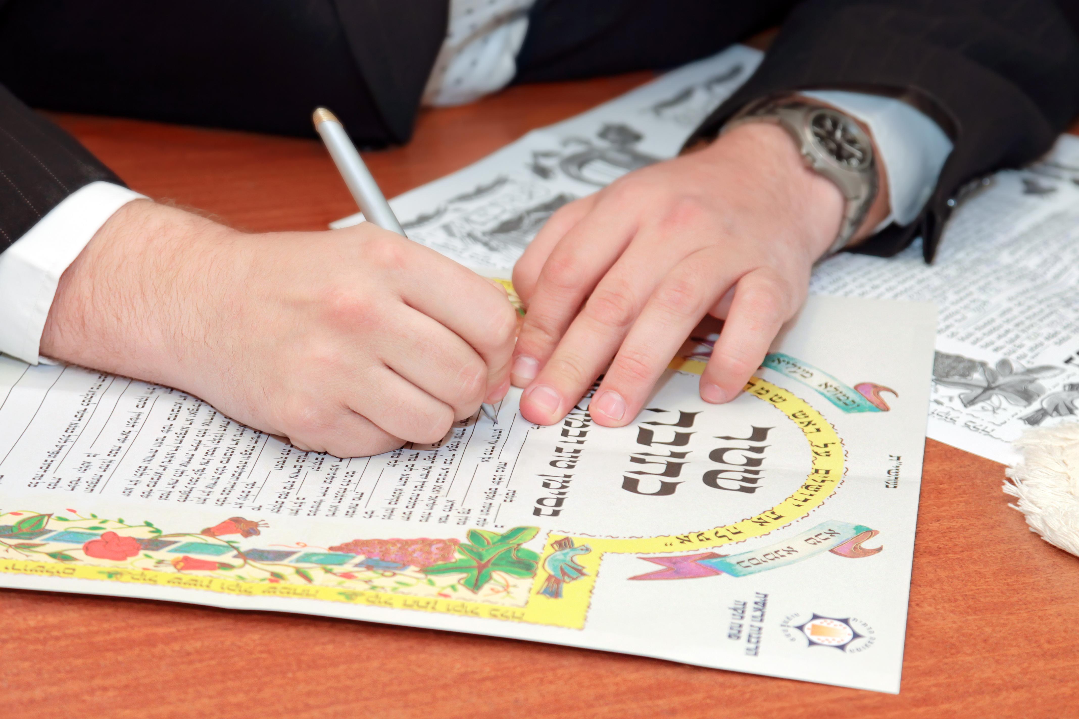 Jewish wedding, signing prenuptial agreement ketubah